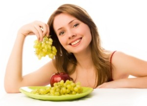 beautiful woman with an apple and grapes